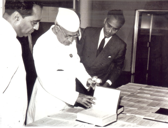 Jawaharlal Nehru, flanked by Homi Bhabha on his right and K. Chandrasekharan on his left, looking at the Ramanujan Notebooks published by TIFR.Courtesy TIFR Archives