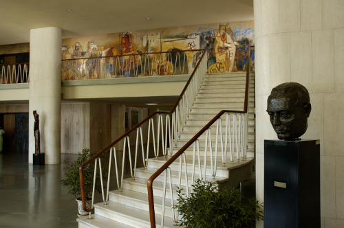 Stairs to the Library floor showing the wall mural by M.F. Hussain; the bust of Homi Bhabha can be seen on the right. TIFR Archives